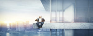 Man drinking coffee on the border of the skyscraper